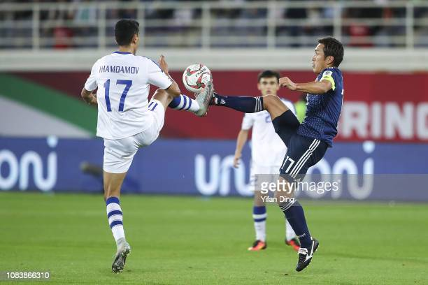 Toshihiro Aoyama of Japan and Dostonbek Khamdamov of Uzbekistan fight for the ball during the AFC Asian Cup Group F match between Japan and...