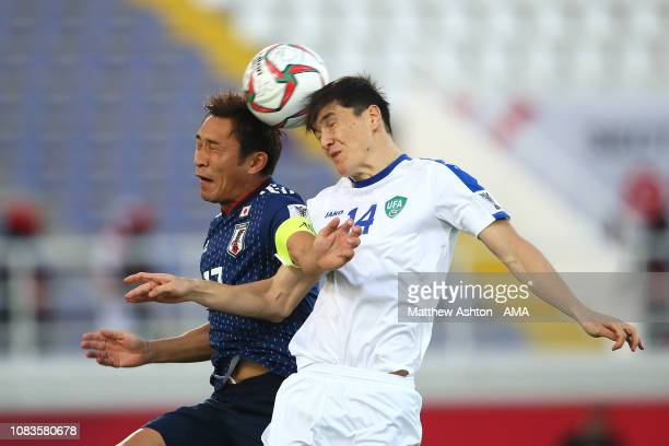Toshihiro Aoyama of Japan competes with Eldor Shomurodov of Uzbekistan during the AFC Asian Cup Group F match between Japan and Uzbekistsn at Khalifa...