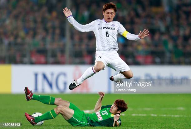 Toshihiro Aoyama of Sanfrecce Hiroshima challenges He Dae Sung of Beijing Guo'an during the AFC Champions match between Sanfrecce Hiroshima and...