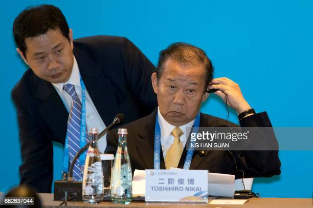 CORRECTION Toshihiro Nikai Secretary General of the Japanese Liberal Democratic Party adjusts his ear piece before a session on connectivity of...