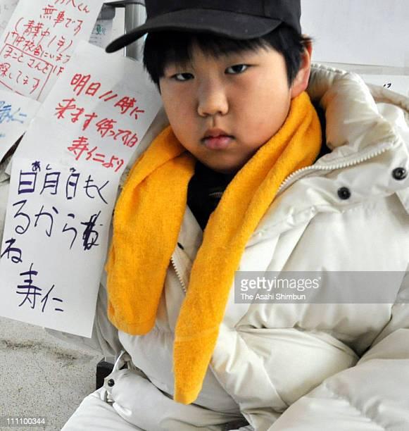 Toshihito Aisawa walks around the evacuation center holding banners writing his missing family members names at Kadonowaki Junior High School on...
