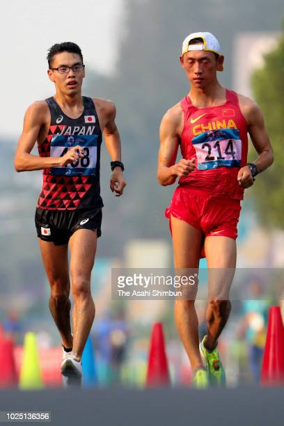 Toshikazu Yamanishi of Japan and Wang Kaihua of China compete in the Race Walk Men's 20km on day eleven of the Asian Games on August 29 2018 in...