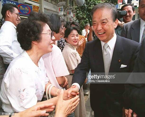 Toshiki Kaifu former Japanese prime minister and president of the main opposition New Frontier Party shakes hands with wellwishers during a campaign...