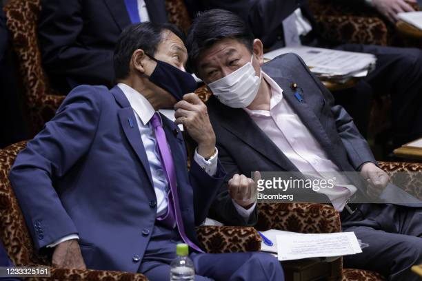 Toshimitsu Motegi, Japan's foreign minister, right, and Taro Aso, deputy prime minister and finance minister, wear protective face masks while...