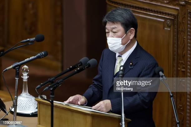 Toshimitsu Motegi, Japan's foreign minister, wears a protective face mask as he delivers a speech during an ordinary session at the lower house of...