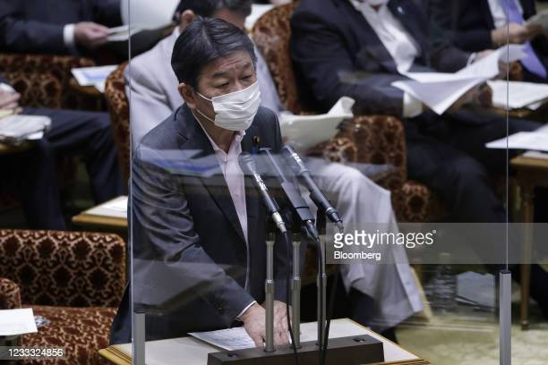 Toshimitsu Motegi, Japan's foreign minister, wears a protective face mask while speaking from behind a transparent screen during an audit committee...
