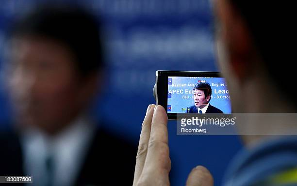 Toshimitsu Motegi, Japan's minister of economy, trade and industry, is seen through a camera viewfinder as he speaks during a news conference...