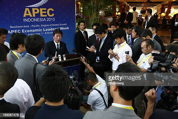 Toshimitsu Motegi, Japan's minister of economy, trade and industry, center left, speaks during a news conference following the Asia-Pacific Economic...