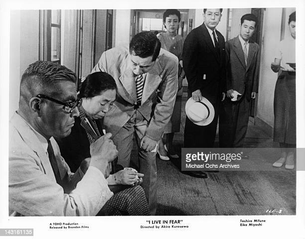 Toshiro Mifune and Eiko Miyoshi waiting in hallway as others watch in a scene from the film 'I Live In Fear' 1955