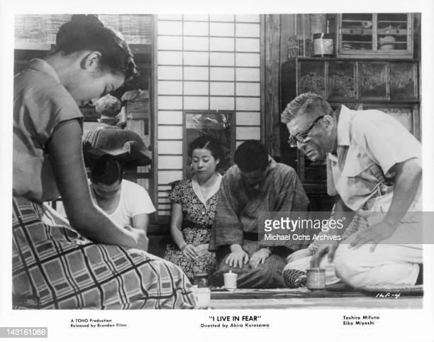 Toshiro Mifune kneeling with family in a scene from the film 'I Live In Fear' 1955