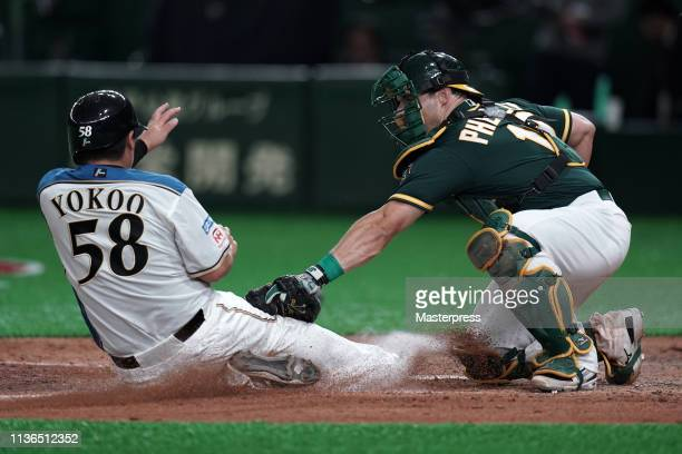 Toshitake Yokoo of the Hokkaido NipponHam Fighters is tagged out by Catcher Josh Phegley of the Oakland Athletics in the bottom of 7th inning during...