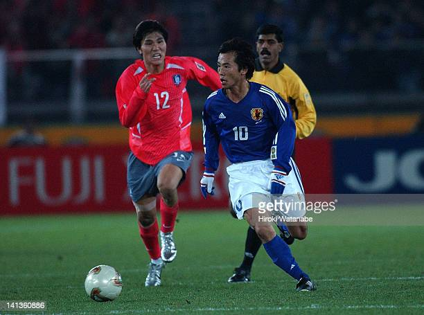 Toshiya Fujita of Japan and Kim DongJin of South Korea compete for the ball during the East Asian Football Championship match between Japan and South...