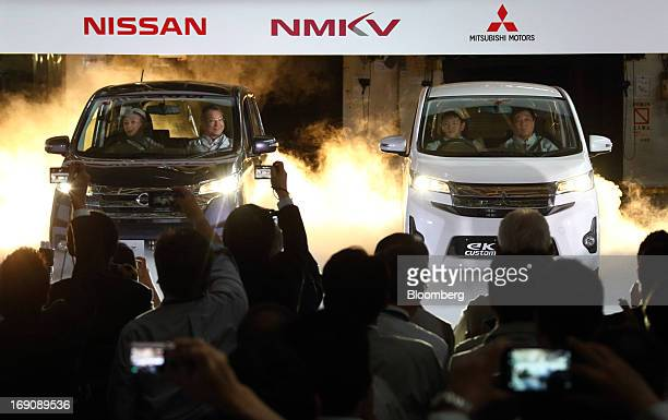 Toshiyuki Shiga chief operating officer of Nissan Motor Co center left rides on the passenger seat of the Nissan DAYZ minicar and Osamu Masuko...