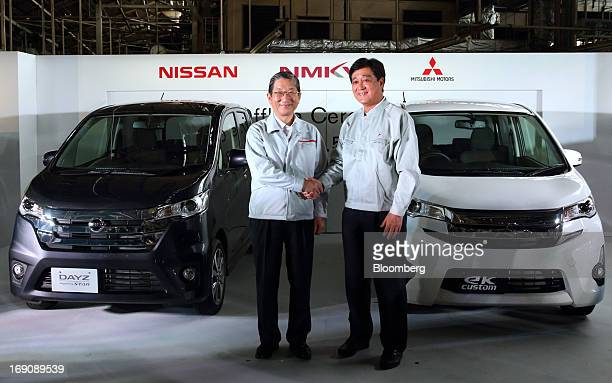 Toshiyuki Shiga chief operating officer of Nissan Motor Co left shakes hands with Osamu Masuko president of Mitsubishi Motors Corp during their...