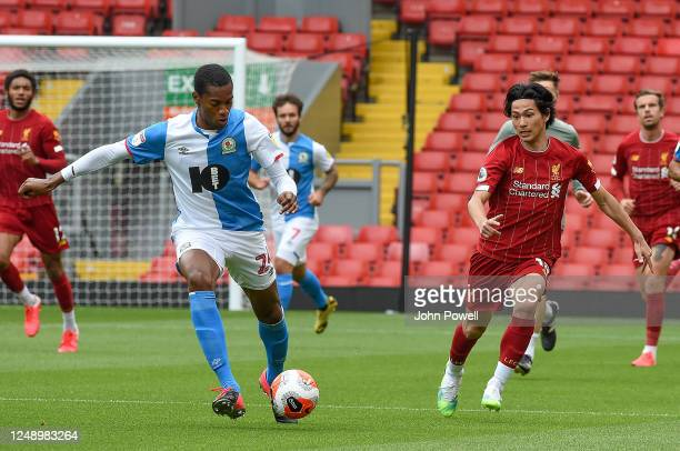 Tosin Adarabioyo of Blackburn Rovers with Takumi Minamino of Liverpool during the game at Anfield on June 11, 2020 in Liverpool, England.