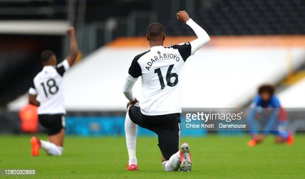 Tosin Adarabioyo of Fulham FC takes a knee before the Premier League match between Fulham and Crystal Palace at Craven Cottage on October 24, 2020 in...