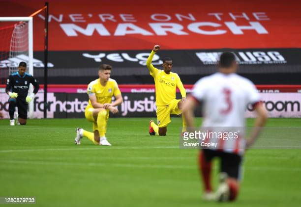 Tosin Adarabioyo of Fulham takes a knee in support of the Black Lives Matter movement prior to the Premier League match between Sheffield United and...