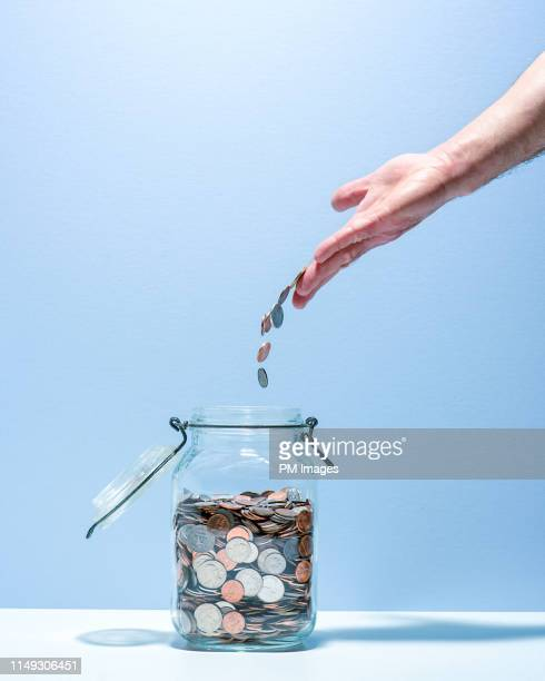 tossing pocket change into jar - dime stock pictures, royalty-free photos & images