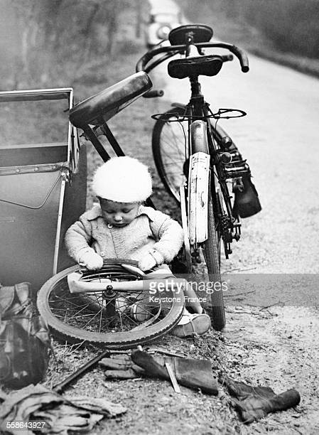 A tot whose cycle side car had broken down endeavours to repair a puncture on the roadside near the city of Dorking in March 1937 in United Kingdom