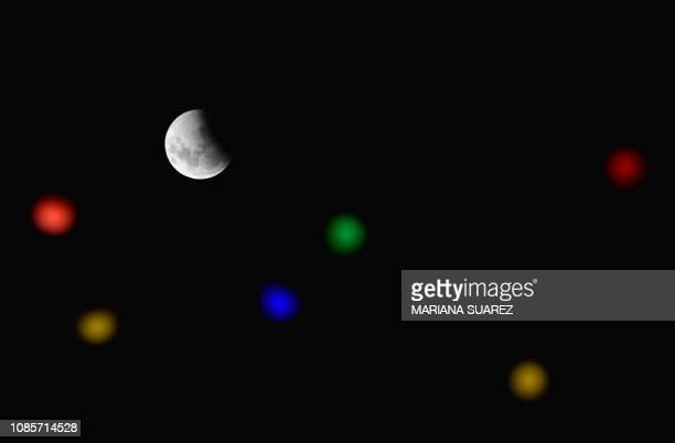 TOPSHOT A total eclipse begins as the full moon shines over Montevideo on January 21 2019 while colour lights decorate 18 de julio Avenue ahead of...
