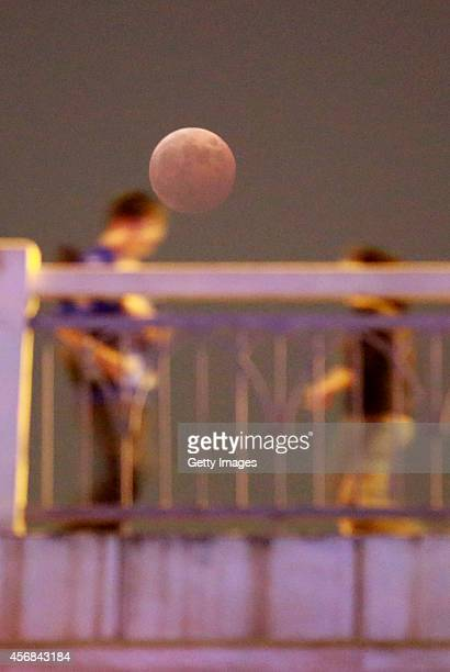 Total eclipse of the moon is seen on October 08 2014 in Wuhan Hubei province of China The moon turns red and halfshadowed during total lunar eclipse...