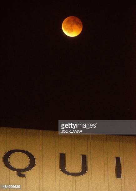 Total eclipse of the moon underway over southern California as seen from Korea town west of downtown Los Angeles early on April 15 2014 The entire...