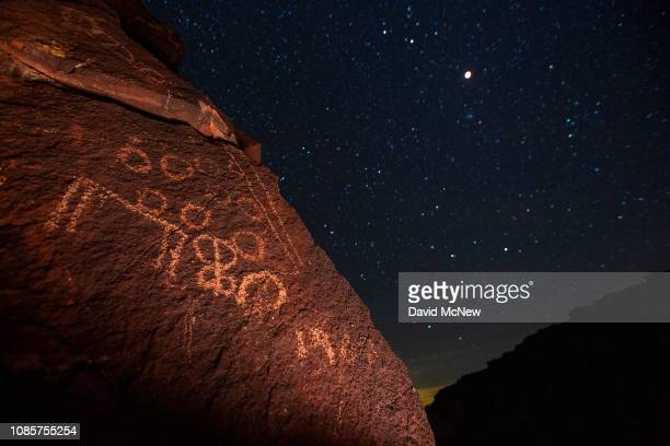 Total lunar eclipse and supermoon is seen over an ancient Native American petroglyph which has been graffitied to read '1989' on January 20, 2019...