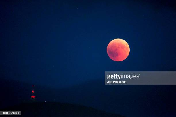 A total lunar eclipse is seen above a television tower on top of the Patscherkofel mountain near Innsbruck the capital town of Tyrol on July 27 2018...