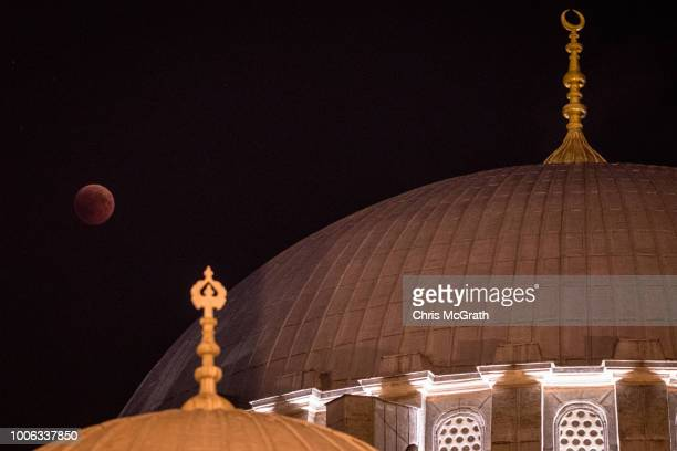 A total lunar eclipse is seen behind a dome of Istanbul's famous Suleymaniye Mosque on July 27 2018 in Istanbul Turkey The total lunar eclipse was...