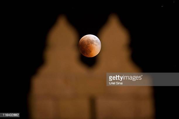 A total lunar eclipse is seen through the old city walls on June 15 2011 in Jerusalem Israel The longest lunar eclipse for a decade took place...
