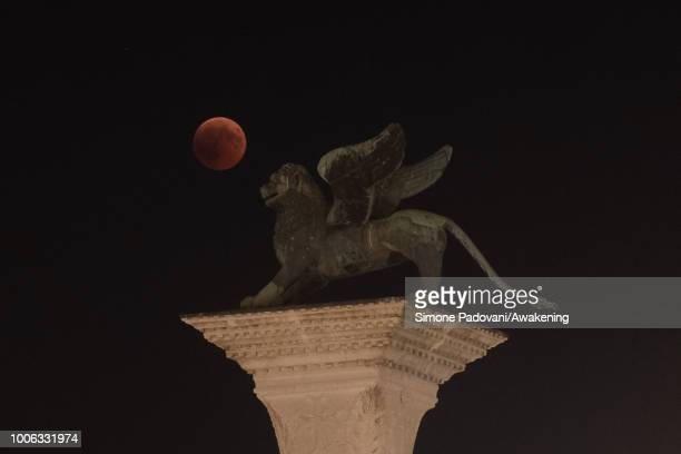 A total lunar eclipse is seen up the sky on the Venetian lagoon over the lion of San Marco in St Mark square on July 27 2018 in Venice Italy The...
