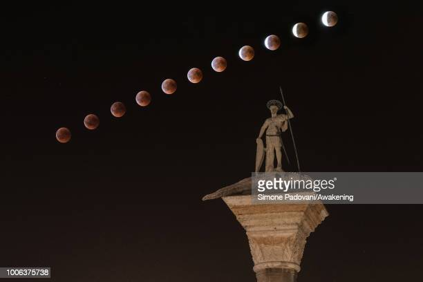 A total lunar eclipse is seen up the sky on the Venetian lagoon over the statue of San Todaro in St Mark square on July 27 2018 in Venice Italy The...