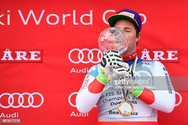 Total winner of the FIS Downhill World Cup Beat Feuz of Switzerland kisses the trophy on the podium after the Men's Downhill of the FIS World Cup...