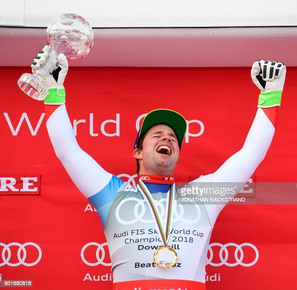 Total winner of the FIS Downhill World Cup Beat Feuz of Switzerland celebrates on the podium with his trophy after the Men's Downhill of the FIS...