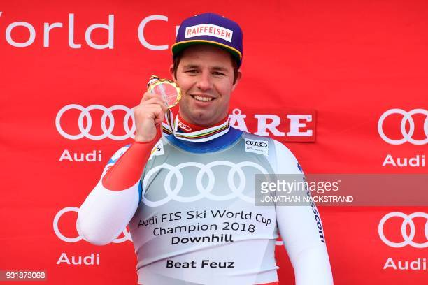 Total winner of the FIS Downhill World Cup first place Switzerland's Beat Feuz poses on the podium after the Men's Downhill of the FIS World Cup...
