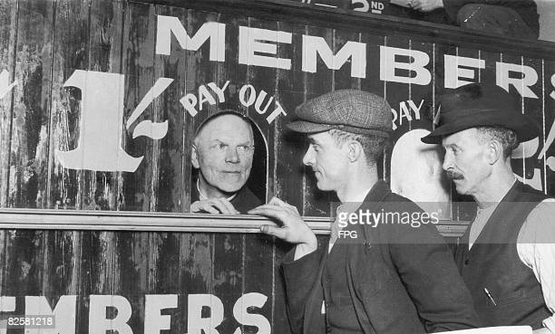 10th November 1932 The Reverend Father Carless pays out tote winnings at the St Anne's Social Club in London's Docklands He organised the club...