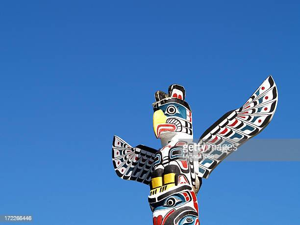 totem against blue sky - totem pole stock photos and pictures