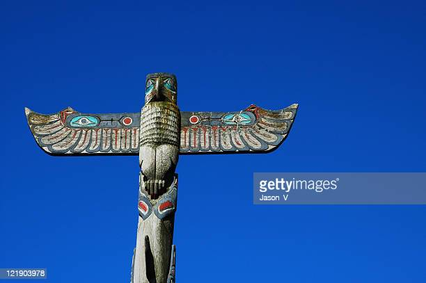 totem pole with blue sky - totem pole stock photos and pictures