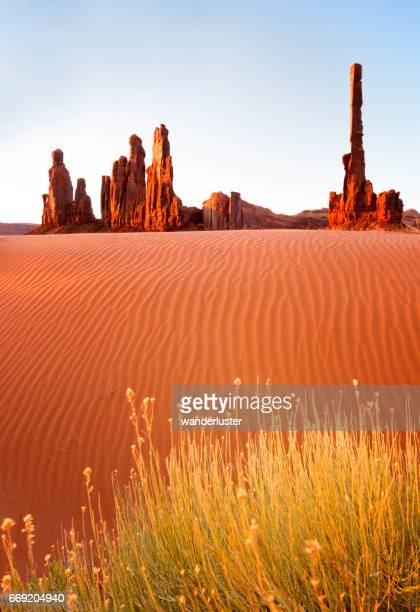 Totem Pole with rippled sand dunes at sunrise, Monument Valley, Arizona, USA