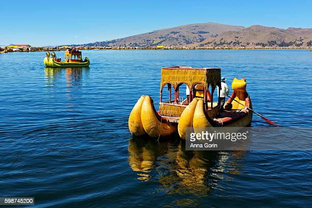 """Totora raft offers tourists a boat ride on Lake Titicaca offshore of the """"floating islands"""" in Puno district of Peru"""