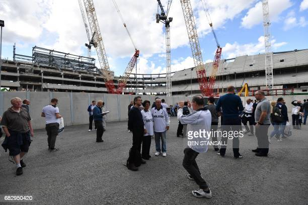 Tottenham fans take photographs outside the site where a new stadium is being constructed next to White Hart Lane in London on May 14 2017 ahead of...