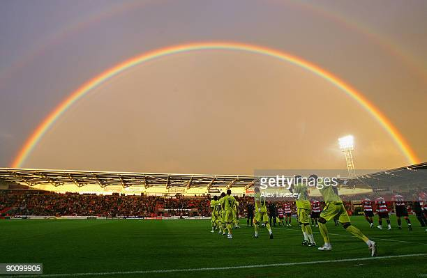 Tottenham Hotspur and Doncaster Rovers players run on to the pitch as a rainbow arcs over Keepmoat Stadium before the Carling Cup second round match...