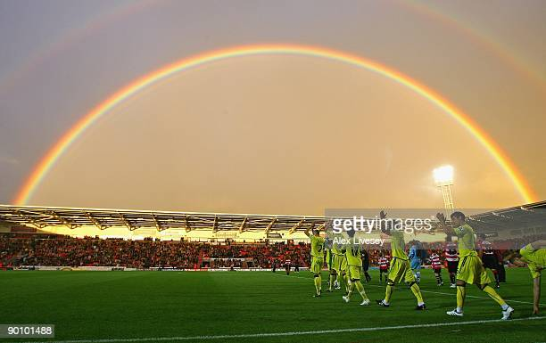 Tottenham Hotspur and Doncaster Rovers players run on to the pitch as a rainbow arches over the Keepmoat Stadium before the Carling Cup second round...