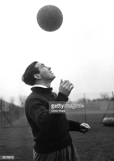Tottenham Hotspur and England footballer Alf Ramsey practices his heading skills at the training ground