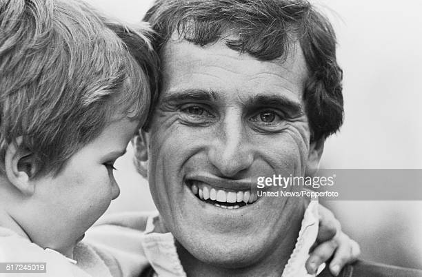 Tottenham Hotspur and England goalkeeper Ray Clemence pictured holding a child at a Spurs training session in London on 10th March 1982