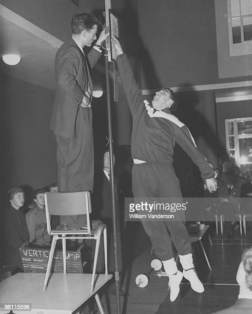 Tottenham Hotspur centreforward Bobby Smith undergoes a power test by leaping and stretching with a vertical jump during a 'Keep Fit' conference held...