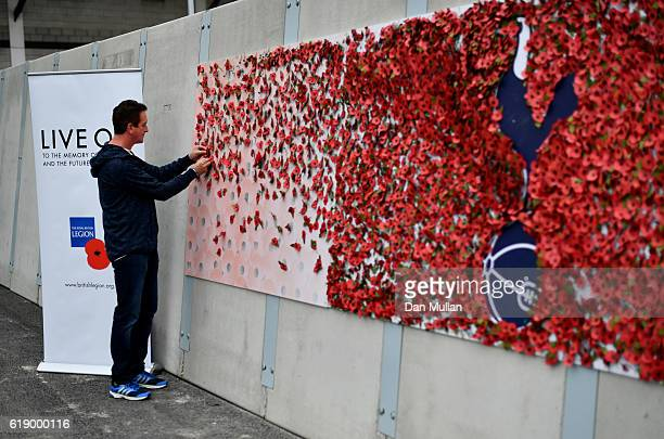 Tottenham Hotspur fans attaches a paper poppy around the clubs badge ahead of the Rememberance Day prior to the Premier League match between...