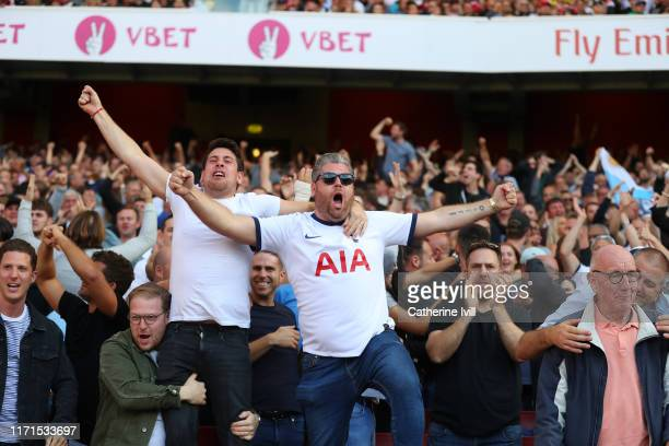 Tottenham Hotspur fans celebrate their teams first goal during the Premier League match between Arsenal FC and Tottenham Hotspur at Emirates Stadium...