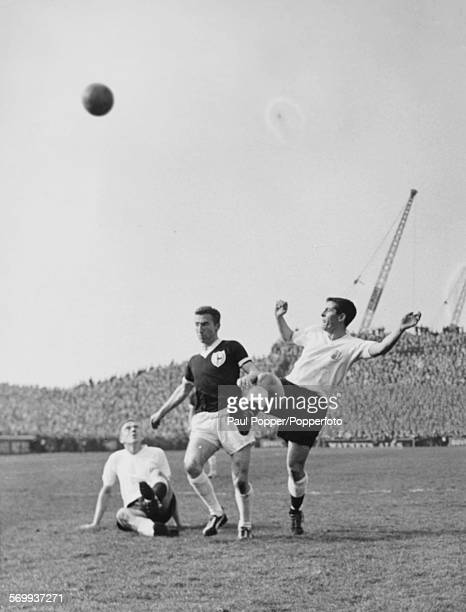 Tottenham Hotspur football player Cliff Jones beats Fulham players Alan Mullery and Jim Langley to the ball during a match at Fulham FC's ground...