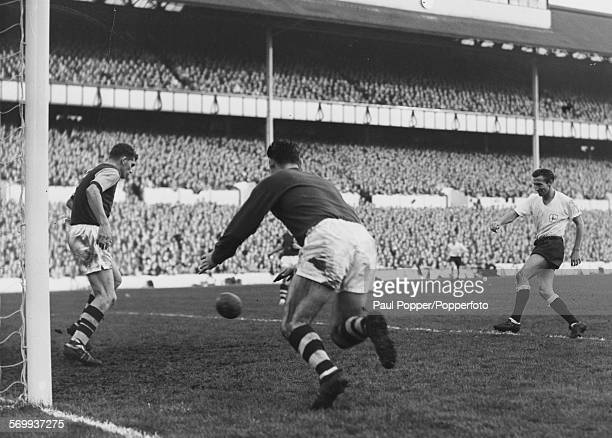 Tottenham Hotspur football player Cliff Jones fails to score as Burnley player Brian Miller kicks the ball away from the goal line with Burnley...